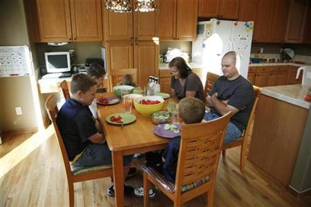 Zachary Frantzen (L) prays with his family before dinner in Longmont, Colorado July 19, 2010. REUTERS/Rick Wilking