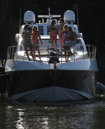 Guests enjoy the warm weather on a private yacht on the Potomac River in Washington, September 6, 2010. REUTERS/Molly Riley