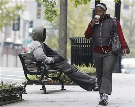 A woman passes by a homeless man sitting on a bench in Washington, October 20, 2010. REUTERS/Stelios Varias
