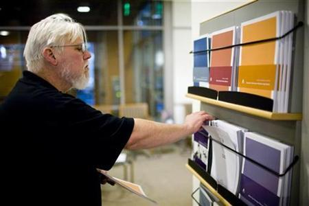 California state worker Curtis Walker looks over retirement plan brochures at the Calpers regional office in Sacramento, California October 21, 2009. REUTERS/Max Whittaker