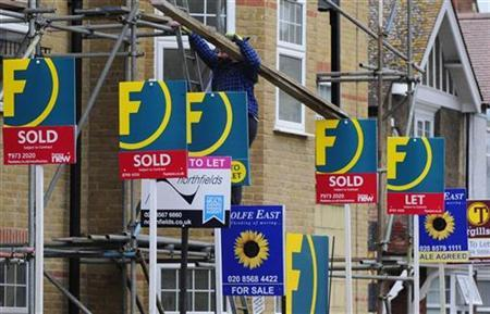 A man carries wood up scaffolding near For Sale and To-Let signs in west London February 9, 2010. REUTERS/Toby Melville