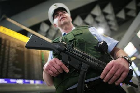 A police officer patrols inside the main terminal of Frankfurt's airport, November 17, 2010. REUTERS/Alex Domanski