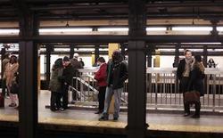 <p>Люди ждут поезд в нью-йоркской подземке 12 декабря 2009 года. Торговец бакалейной лавки спрыгнул на пути метро и спас неудачно упавшего в обморок пассажира, не желая опаздывать на работу и терять зарплату. REUTERS/Lucas Jackson</p>