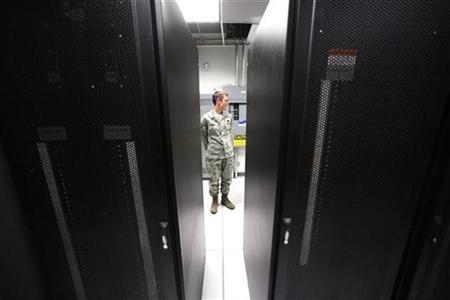Airman Damon Schmidt (L) infrastructure tech talks with a colleague (not seen) in the server room at the Air Force Space Command Network Operations & Security Center at Peterson Air Force Base in Colorado Springs, Colorado July 20, 2010. REUTERS/Rick Wilking