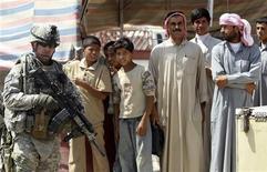 <p>Американский солдат стоит рядом с мирными жителями в поселке под Багдадом, 5 сентября 2010 года. Высокопоставленные чиновники в США разочарованы неспособностью союзников на Ближнем Востоке обрубить канал финансирования террористов и считают главным донором Саудовскую Аравию, сообщила в воскресенье газета со ссылкой на секретные дипломатические депеши. REUTERS/Saad Shalash</p>