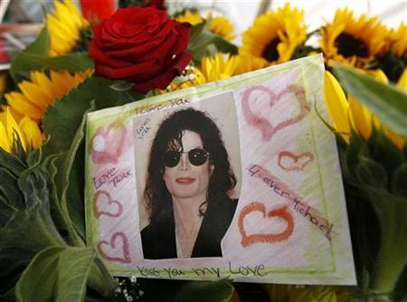 A card with a photograph of late entertainer Michael Jackson is placed among flowers during an event to commemorate the first anniversary of his death, in Leipzig, June 25, 2010. REUTERS/Fabrizio Bensch