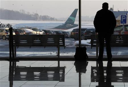 A passenger looks at the snow-covered tarmac of Zaventem international airport near Brussels December 20, 2010. REUTERS/Francois Lenoir (BELGIUM - Tags: TRANSPORT ENVIRONMENT)