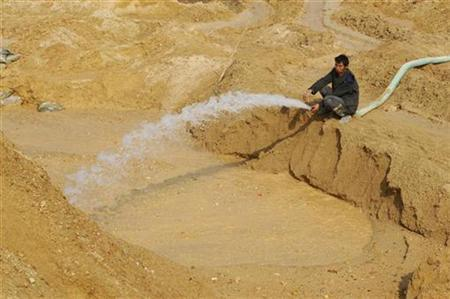 A labourer hoses water into the site of a rare earth metals mine at Nancheng county, Jiangxi province December 21, 2010. REUTERS/Stringer CHINA OUT. NO COMMERCIAL OR EDITORIAL SALES IN CHINA