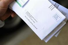 <p>A man holds his envelopes as he waits in line to mail his family's income tax returns at a mobile post office near the Internal Revenue Service building in downtown Washington, April 15, 2010. REUTERS/Jonathan Ernst</p>