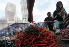 <p>A chilli vendor (C) holds a bunch of chillies as he serves a customer at a market in Jakarta, January 6, 2011. REUTERS/Beawiharta</p>