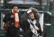 <p>A woman dons her fur hood after coming out of the subway during a snow flurry near Times Square in New York January 7, 2011. REUTERS/Lucas Jackson</p>