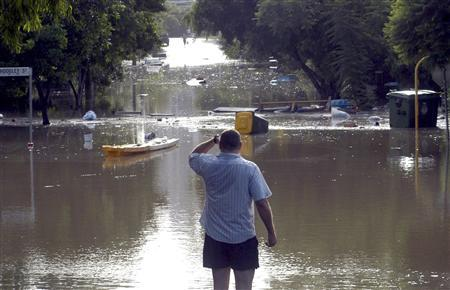 A man looks at debris floating across a flooded street in the inner Brisbane suburb of West End January 12, 2011. REUTERS/ABC News/Giulio Saggin