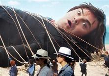 """<p>Mulheres passam em frente de cartaz do filme """"As Viagens de Gulliver"""" com Jack Black, em frente ao hotel Carlton, no Festival de Cannes. 17/05/2010 REUTERS/Christian Hartmann/Arquivo</p>"""