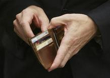 <p>U.S. Treasury Secretary Timothy Geithner puts a piece of foreign currency back in his wallet after showing off the contents of his wallet to a photographer during a break in his testimony before the House Appropriations Subcommittee on General Government and Financial Services on Capitol Hill in Washington, May 21, 2009. REUTERS/Jim Bourg</p>