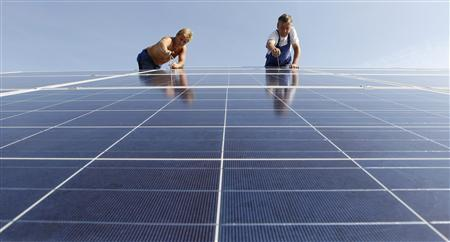 Construction workers fix solar panels for a new solar power plant near Olching-Esting west of Munich in this July 7, 2010 file photo. REUTERS/Michaela Rehle/Files