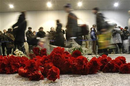 Passengers walk past flowers left on a floor in memory of those killed in Monday's blast at Moscow's Domodedovo airport January 25, 2011. President Dmitry Medvedev blamed airport managers on Tuesday for failing to stop an attack on Russia's busiest international airport which killed 35 people on Monday. REUTERS/Tatyana Makeyeva (RUSSIA - Tags: CRIME LAW TRANSPORT)