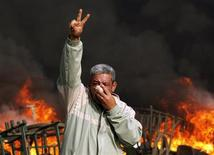 <p>A protester gestures in front of a burning barricade during a demonstration in Cairo January 28, 2011. Police and demonstrators fought running battles on the streets of Cairo on Friday in a fourth day of unprecedented protests by tens of thousands of Egyptians demanding an end to President Hosni Mubarak's three-decade rule. REUTERS/Goran Tomasevic</p>