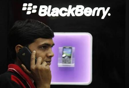 A man speaks on a BlackBerry mobile phone inside a shop in Kolkata January 31, 2011. REUTERS/Rupak De Chowdhuri