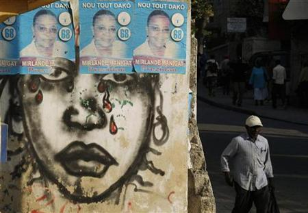 A Haitian man walks next to posters of Haiti's presidential candidate Mirlande Manigat in Port-au-Prince January 19, 2011. Haitian President Rene Preval had reservations about a report from the Organisation of American States (OAS) that challenges the official results of Haiti's chaotic November elections, an official said last Thursday, January 13. REUTERS/Eduardo Munoz