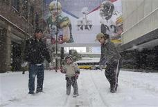 <p>Kevin New (L) from Tampa, Florida plays in the snow with his son Skylar (C) and wife Anne outside their hotel after an overnight storm dropped five inches of snow in Dallas, Texas, February 4, 2011. REUTERS/Gary Hershorn</p>