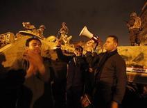 <p>Демонстранты стоят в окружении военных в Каире, 6 февраля 2011 года. Египетские власти начали переговоры с оппозицией на фоне длящихся уже почти две недели антиправительственных демонстраций, участники которых требуют отставки президента Хосни Мубарака. REUTERS/Asmaa Waguih</p>