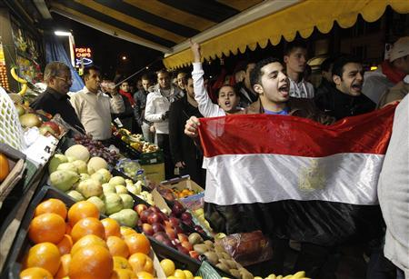 Egyptians and supporters celebrate the resignation of Egypt's President Hosni Mubarak as they pass a fruit and vegetable stand on the Edgeware Road in London February 11, 2011. REUTERS/Luke MacGregor