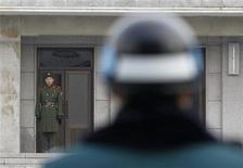 <p>A North Korean soldier looks south, as a South Korean soldier (front) stands guard, at the truce village of Panmunjom in the demilitarised zone separating the two Koreas in Paju, about 55 km (34 miles) north of Seoul, December 8, 2010. REUTERS/Jo Yong-Hak</p>