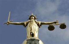 <p>The Statue of Justice, depicted as a women with a sword in one hand and scale in her other, is seen on top of the London Central Criminal Court, the Old Bailey in London August 12, 2005. REUTERS/Russell Boyce</p>