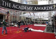 <p>Trabalhadores da American Turf & Carpet instalam o tapete vermelho durante os preparativos para o 83o Academy Awards, em Hollywood, em 23 de fevereiro de 2011. REUTERS/Danny Moloshok</p>
