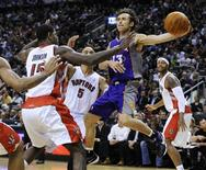 <p>Phoenix Suns Steve Nash passes the ball off around Toronto Raptors Amir Johnson (L), Jerryd Bayless (back), and James Johnson (R) during the first half of their NBA basketball game in Toronto February 25, 2011. REUTERS/Mark Blinch</p>
