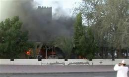 <p>Мужчина фотографирует горящее здание в Сохаре (Оман), 27 февраля 2011 года. Участники политических демонстраций в Омане заблокировали в понедельник дорогу к главному экспортному порту страны и НПЗ. REUTERS/via Reuters TV</p>