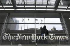 <p>A window washer cleans the windows above the front door of the New York Times building in New York, March 26, 2010. REUTERS/Gary Hershorn</p>