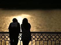 <p>A couple watch a sunset near a lake in Putrajaya December 22, 2008. REUTERS/Bazuki Muhammad</p>