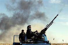 <p>Повстанцы стреляют из зенитного орудия на дороге между Брегой и Рас-Лануфом 12 марта 2011 года. Франция активизирует попытки убедить мировые державы закрыть для полетов воздушное пространство над Ливией, где войска Муаммара Каддафи в понедельник сражаются с повстанцами за контроль над имеющим стратегическое значение для нефтяной сферы страны городом Марса-эль-Брега. REUTERS/Goran Tomasevic</p>