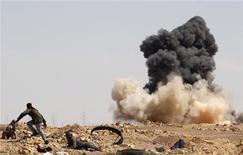 <p>Иностранный журналист и повстанец бегут в укрытие во время авиаударов на дороге между городами Брега и Рас-Лануф, 12 марта 2011 года. Войска, поддерживающие ливийского лидера Муаммара Каддафи, нанесли во вторник как минимум четыре авиаудара по городу Адждабия на востоке страны, сообщил телеканал Al Jazeera. REUTERS/Goran Tomasevic</p>