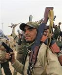 <p>Un soldado del Gobierno libio sostiene sus armas en la ciudad de Ajdabiyah. mar 16 2011. Cuando comienzan los disparos por la noche en Trípoli, las autoridades gubernamentales se apresuran a decir que no hay necesidad de alarmarse: son sus seguidores disparando al aire para celebrar la última victoria de Muammar Gaddafi sobre los rebeldes. REUTERS/Ahmed Jadallah</p>
