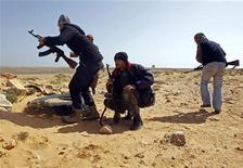 <p>Ливийские мятежники во время столкновений на дороге к Рас-Лануфу 10 марта 2011 года. Египетская армия с ведома Вашингтона начала переправлять через границу оружие для ливийских мятежников, сообщила в пятницу американская газета The Wall Street Journal. REUTERS/Goran Tomasevic</p>