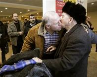 <p>A passenger (R) from the Georgian Airways flight from Tbilisi, is greeted by an unidentified man as he leaves the custom zone at Moscow's Domodedovo airport after landing January 8, 2010. REUTERS/Sergei Karpukhin</p>