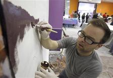 <p>Volunteer painter Pete Sosalski brushes paint onto a canvas for the Philadelphia International Airport gateway mural during a public painting session in Philadelphia, March 12, 2011. REUTERS/Tim Shaffer</p>