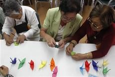 <p>Rosa Arashiro (C) and Hiruko Omura (R) make origami cranes to support Japan's earthquake and tsunami victims at the Peruvian Japanese Cultural Center in Lima, March 18, 2011. REUTERS/Mariana Bazo</p>