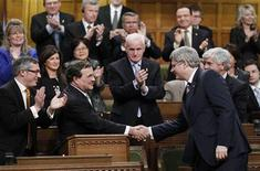 <p>Canada's Finance Minister Jim Flaherty (2nd R) shakes hands with Prime Minister Stephen Harper after delivering his budget as Minister of Industry Tony Clement (L) and Foreign Affairs Minister Lawrence Cannon (R) applaud in the House of Commons on Parliament Hill in Ottawa March 22, 2011. REUTERS/Chris Wattie</p>