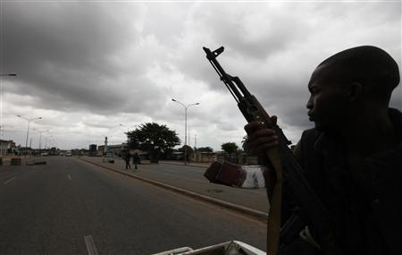 A pro-Ouattara fighter from a group which calls itself the ''invisible commandos'' holds a weapon during a patrol on a street in northern Abidjan's Abobo district, March 26, 2011. REUTERS/Luc Gnago