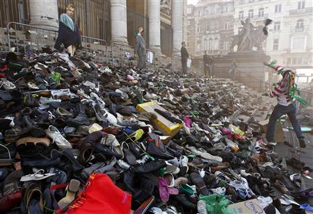 A worker in the non-profit sector, which includes nurses and social workers, throws his shoes onto the steps of the stock exchange building, during a protest in Brussels, March 29, 2011. REUTERS/Thierry Roge