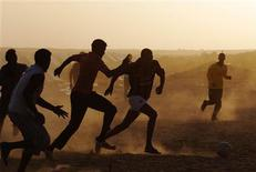 <p>Foreign evacuees, who fled the unrest in Libya, play soccer at a refugee camp near the Libyan and Tunisian border crossing of Ras Jdir March 29, 2011. REUTERS/Anis Mili</p>