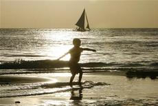 <p>A boy skimboards on the shore on the resort island of Boracay in Malay in the province of Aklan, central Philippines, November 21, 2009. REUTERS/Romeo Ranoco</p>