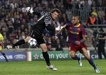 <p>Daniel Alves passa pelo goleiro do Shakhtar Donetsk parar marcar um dos gols do Barcelona na vitória de 5 x 1 na Liga dos Campões, em Barcelona. 06/04/2011 REUTERS/Albert Gea</p>