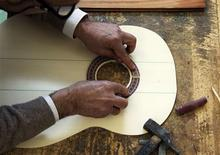 "<p>Jose Luis Cebillo, workshop manager of the Manuel Rodriguez and Sons' guitar factory, places a rosette to decorate a sound hole of a guitar in Esquivias, near Madrid, March 17, 2011. In a small town in La Mancha, the region that inspired the epic Spanish novel ""Don Quixote"", the third generation guitar-maker is struggling to secure the future of his business. Toledo-based Manuel Rodriguez and Son is still making handmade guitars and exports 90 percent of its production to 120 countries. Many of its finest guitars have found their way into the hands of famous musicians, world leaders, Nobel Prize-winners and royalty. REUTERS/Sergio Perez</p>"