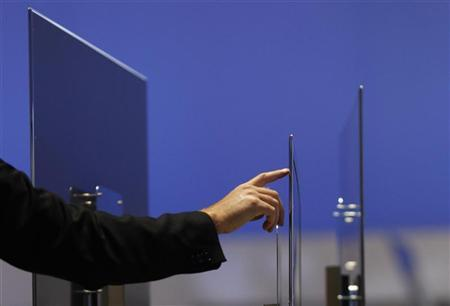 A visitor touches an ultra slim flat screen TV by Samsung at the Internationale Funkausstellung (IFA) consumer electronics fair at ''Messe Berlin'' exhibition centre in Berlin, September 3, 2010. REUTERS/Christian Charisius