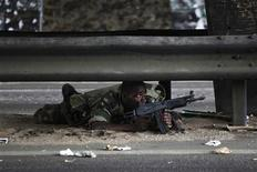 <p>A soldier loyal to Ivory Coast presidential claimant Alassane Ouattara lies on a road as fighting flares across the country's main city Abidjan April 4, 2011. REUTERS/Emmanuel Braun</p>