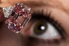 <p>An employee poses with a 24.78 carat Fancy Intense Pink diamond at Sotheby's in Geneva November 10, 2010. REUTERS/Valentin Flauraud</p>